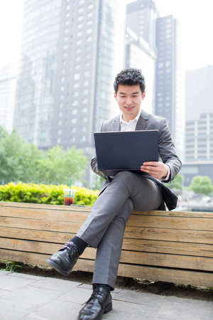 Young businessman working with laptop outdoors LANG_EVOIMAGES