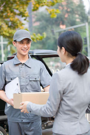 cardboard only: Young woman getting a package from delivery person