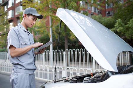 class maintenance: Auto mechanic repairing car