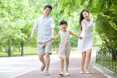 Happy young family walking together in park