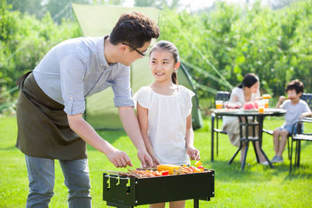 sitting area: Young family barbecuing outdoors