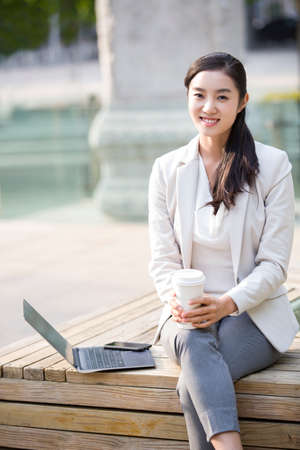 Young businesswoman working with laptop outdoors
