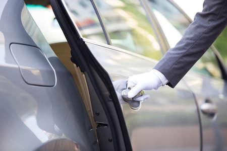 designated: Chauffeur opening car door LANG_EVOIMAGES