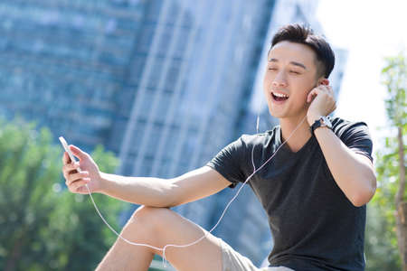 Young man listening to music with a smart phone LANG_EVOIMAGES