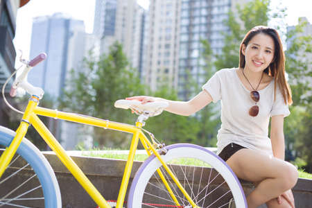 Happy young woman and bicycle