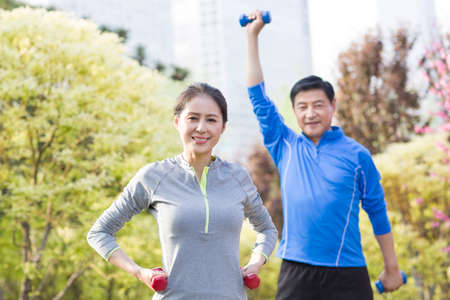 Happy mature couple exercising with dumbbell in park