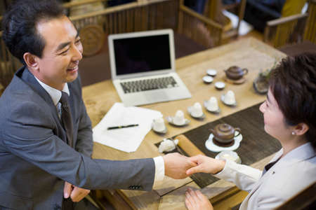 mid afternoon: Business person shaking hands in tea room LANG_EVOIMAGES