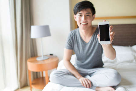 Young man showing smart phone on bed