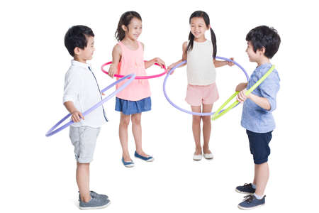 Happy children spinning plastic hoops LANG_EVOIMAGES