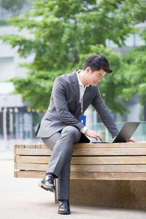 cardkey: Young businessman working with laptop outdoors LANG_EVOIMAGES