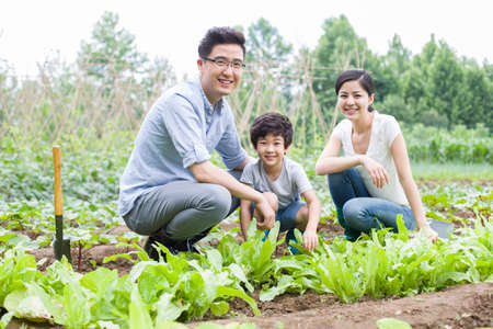 Young family gardening together LANG_EVOIMAGES