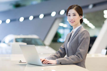 technology: Confident receptionist using laptop at reception counter LANG_EVOIMAGES