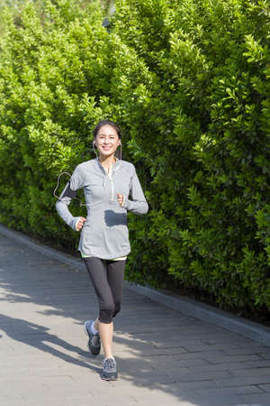 one female: Happy mature woman running and listening to music in park LANG_EVOIMAGES