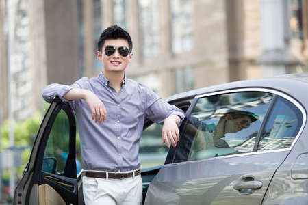 transportation: Young man standing next to his car