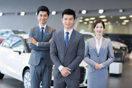 looking for job: Confident salespeople standing with new cars in showroom LANG_EVOIMAGES