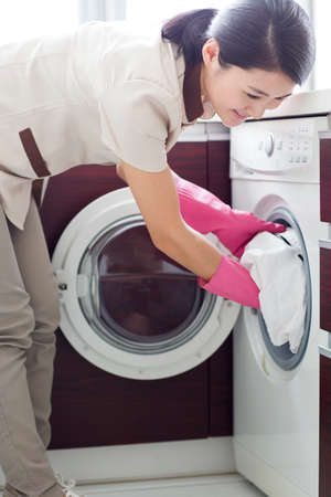 cleaning service: Domestic staff doing laundry LANG_EVOIMAGES