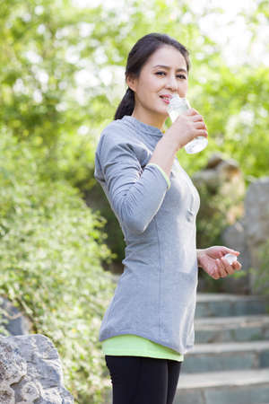 Happy mature woman drinking water after exercising