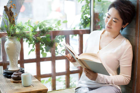 food drink industry: Mid adult woman reading book in tea room