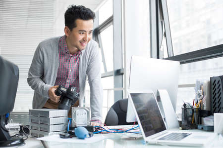 behind scenes: Male photographer working in office