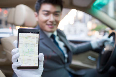designated: Chauffeur using smart phone as gps navigation for car LANG_EVOIMAGES