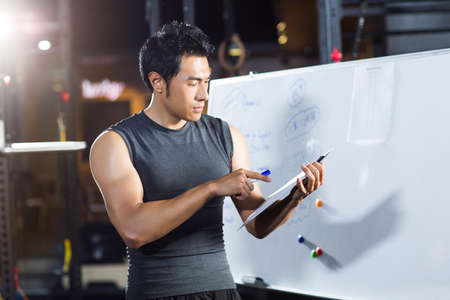 adult  body writing: Coach making exercise plan in gym
