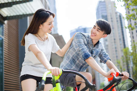 road cycling: Happy young couple riding bicycles
