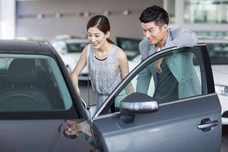 drivers seat: Young couple looking at new car in showroom LANG_EVOIMAGES