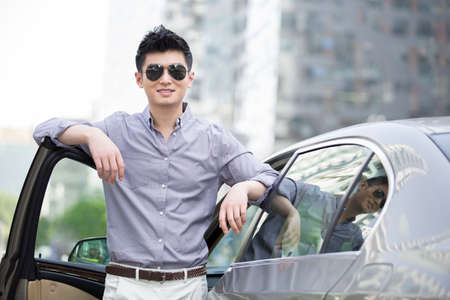 automobile door: Young man standing next to his car