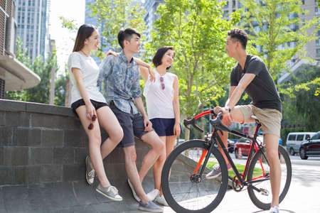 road cycling: Happy young adults talking together LANG_EVOIMAGES