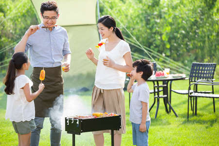 cup four: Young family barbecuing outdoors