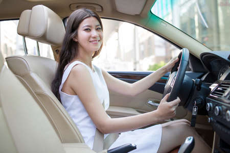drivers seat: Young woman driving car LANG_EVOIMAGES
