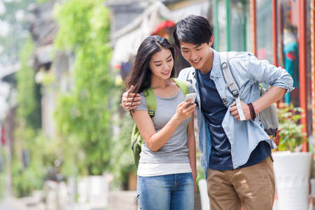 back alley: Young couple travelling in Beijing Hutong with smart phone