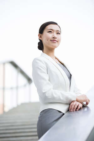 staircases: Businesswoman looking at view thinking LANG_EVOIMAGES