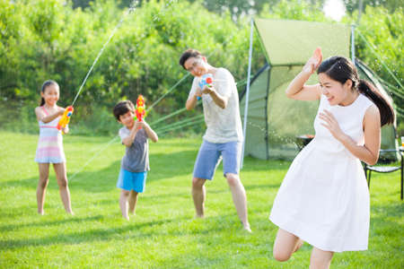 Happy young family playing squirt guns