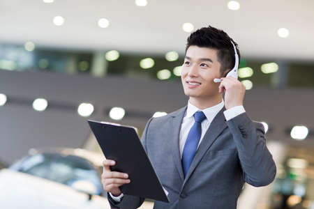 Confident car salesman with headset LANG_EVOIMAGES