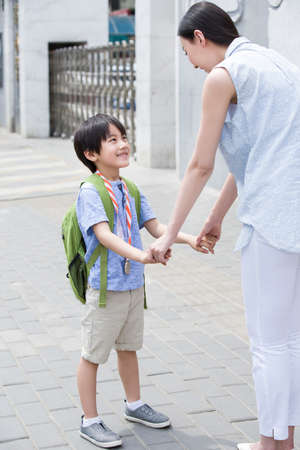 Mother picking her son up from school LANG_EVOIMAGES