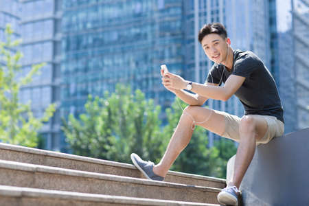 staircases: Young man listening to music with a smart phone LANG_EVOIMAGES