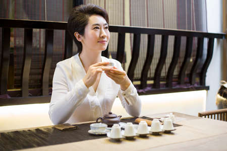 mid afternoon: Mid adult woman performing tea ceremony