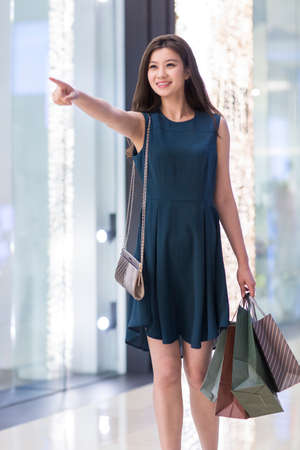 Happy young woman shopping LANG_EVOIMAGES
