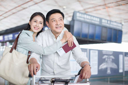 Mature couple waiting at airport LANG_EVOIMAGES