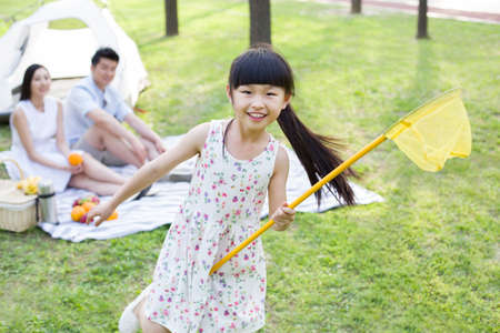 sitting area: Happy girl playing on grass with butterfly net LANG_EVOIMAGES