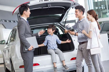 new age: Young family choosing car in showroom LANG_EVOIMAGES