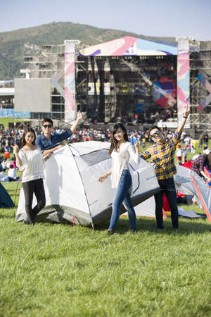 looking away from camera: Chinese friends setting up a tent on the grass LANG_EVOIMAGES
