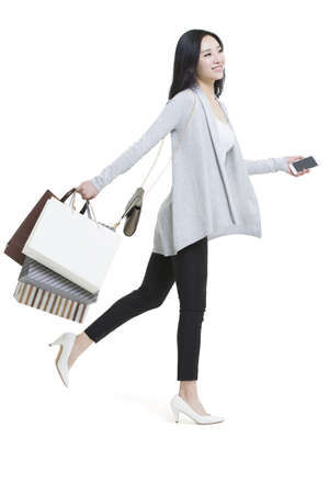 touchscreen: Happy young woman holding a smart phone and shopping bags