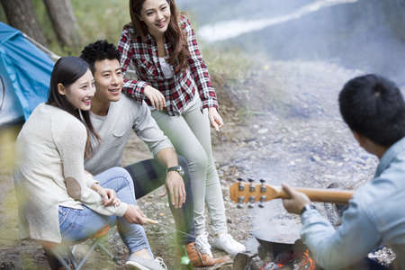 Young Chinese friends sitting around campfire playing guitar