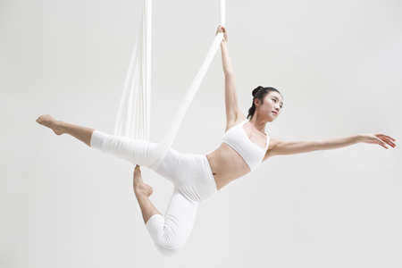 coordinacion: Young woman practicing aerial yoga