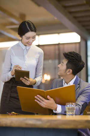 drinks after work: Young Chinese man ordering in restaurant LANG_EVOIMAGES