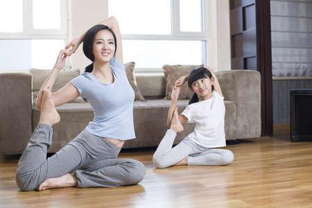 buena postura: Joven madre e hija haciendo yoga en casa LANG_EVOIMAGES