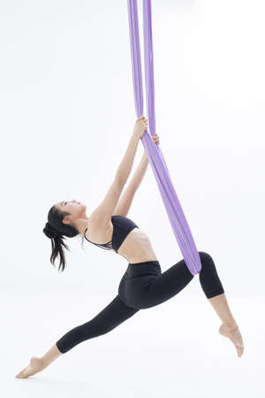 pull out: Young woman practicing aerial yoga