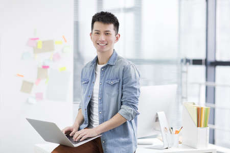 Young Chinese man using laptop in office